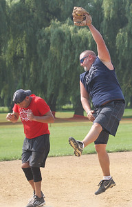 "Candace H. Johnson-For Shaw Media Gurnee Fire's Jim Pellitteri is safe on third as Gurnee Police's Brian Fiene takes the throw during the Gurnee Days ""Battle of the Badges"" softball game at Viking Park in Gurnee. (8/12/18)"