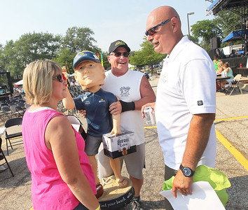 Candace H. Johnson-For Shaw Media Patti and Steve Paddock, of McHenry talk with Lindenhurst Mayor Dominic Marturano after they won a giant bobblehead of Coach Jon Gruden, with the Oakland Raiders, at the Mayor's Auction during Lindenfest at Slove Park in Lindenhurst. (8/11/18)