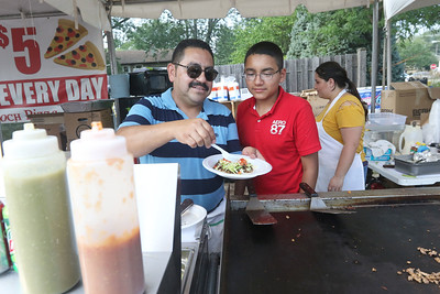 Candace H. Johnson-For Shaw Media Juan Hernandez, of Lake Villa, owner of Supermercado San Judas Inc., makes a steak taco for a customer with his son, Luis, 13, by his side during Lindenfest at Slove Park in Lindenhurst. Maria Carreno, of Round Lake stood behind them helping in the food booth.(8/11/18)