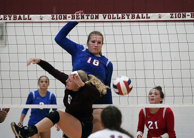 Candace H. Johnson-For Shaw Media Lakes Kelli Rettig (#18) keeps an eye on her attack against Zion-Benton's Morgan Moeller in the second game at Zion-Benton Township High School in Zion. Lakes won 25-16, 25-13. (8/20/18)
