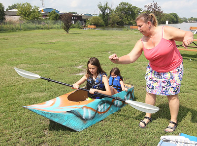 Candace H. Johnson-For Shaw Media Sarah Bernstein, 12, of West Dundee and her sister, Hannah, 6, gets some tips from their aunt, Heather Winandy, of Prospect Heights on how to paddle their boat before competing in the 21st annual Cardboard Boat Race at Lakefront Park in Fox Lake. (8/19/18)