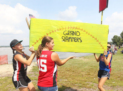 "Candace H. Johnson-For Shaw Media Softball players Tara Levernier, 13, of Spring Grove, Chloe Malveg, 11, of Fox Lake and Jennie Woodruff, 13, of Spring Grove carry their ""Grand Slammers"" boat to the shoreline before competing in the 21st annual Cardboard Boat Race at Lakefront Park in Fox Lake. (8/19/18)"