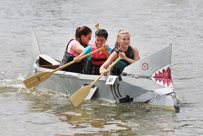 Candace H. Johnson-For Shaw Media Caro Wendt, 23, Marifer Martinec, 18, both of Spring Grove, and Ava Szczesney,14, of Fox Lake paddle their boat called, The Shark, as they compete in the 21st annual Cardboard Boat Race at Lakefront Park in Fox Lake. (8/19/18)
