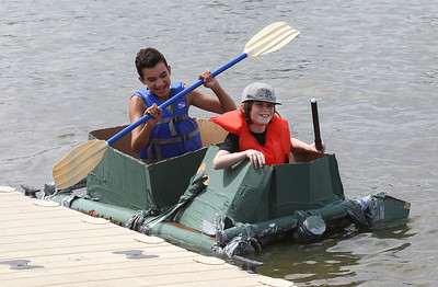Candace H. Johnson-For Shaw Media Robby Schira, of Ringwood and Jason Forman, of Johnsburg, both 14, get to the finish line as they compete during the 21st annual Cardboard Boat Race at Lakefront Park in Fox Lake. (8/19/18)
