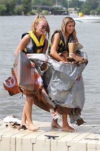 "Candace H. Johnson-For Shaw Media Bre Retherford and Gabby Ross, both 19, of Spring Grove carry their sunken boat called, ""Make Boats Not War,"" on to the pier after competing in one of the races during the 21st annual Cardboard Boat Race at Lakefront Park in Fox Lake. (8/19/18)"