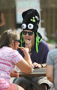 Candace H. Johnson-For Shaw Media Lisa Geyer, of Pittsburg, Pa., enjoys festival food with her nephew, Timmy Walker, of Grayslake as he wears the squid hat he won in a game during Grayslake Summer Days in downtown Grayslake. The event was sponsored by the Grayslake Chamber of Commerce & Industry. (8/18/18)