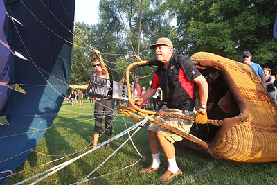 Candace H. Johnson-For Shaw Media Nancy Lemke, of Grayslake helps Alan Zielinski, of Niles inflate his hot air balloon called, Featherlight II, as he holds on to the basket during the 6th Annual Color Aloft Balloon Festival at Central Park in Grayslake.Lemke and her partner, Skip Goss, both pilots, took a ride in the hot air balloon.(8/25/18)