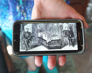 Candace H. Johnson-For Shaw Media Ainsley Wonderling, of Antioch holds a drawing of the inside of the original Lincoln Funeral Car on her phone in the 2015 Lincoln Funeral Car on display in downtown Antioch. The original railcar was destroyed in a fire in 1911.(8/26/18)
