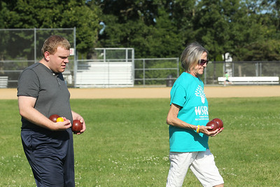 Candace H. Johnson-For Shaw Media Tyler Powers, 24, gets some help carrying bocce balls on the court from Shannon Stolcers, program assistant, both of Gurnee during the first day of Special Olympics Bocce Ball practice next to the Warren Township Center in Gurnee. (7/30/19)
