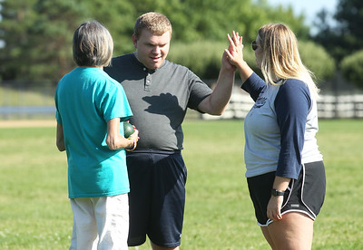 Candace H. Johnson-For Shaw Media Shannon Stolcers, program assistant, talks with Tyler Powers, 24, as he gets a high-five from Katy Wells, program lead, all of Gurnee, during the first practice of Special Olympics Bocce Ball for the season next to the Warren Township Center in Gurnee. (7/30/19)