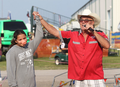 Candace H. Johnson-For Shaw Media Kailyn Lopez, 12, of Harvard wears an honorary pig nose as she gets congratulated by Charlie Boger, swine master, after her section's pig won a Ham Bone Express Pig Race during the Lake County Fair at the Lake County Fairgrounds in Grayslake. (7/25-7/28/19)