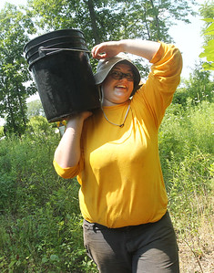 Candace H. Johnson-For Shaw Media Nora Keefe, 16, of Round Lake Beach carries a bucket of water to water newly planted native plants during a Youth Conservation Corps 2019 project near the Rollins Savanna Native Seed Nursery on Washington Street in Grayslake. (7/25/19)