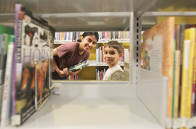 Candace H. Johnson-For Shaw Media Haley Portillo, 18, of Round Lake and her brother, Mark, 5, look through the opening of a bookshelf as they pick out books in the Youth Services Department on the lower level during opening day of the new Lake Villa District Library at 140 N. Munn Road in Lindenhurst.  (8/5/19)