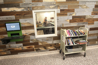 Candace H. Johnson-For Shaw Media A wall of reclaimed wood frames Michelle Koenings, of Lindenhurst, shelving manager, as she works in the automated materials handling (AMH) room during opening day of the new Lake Villa District Library at 140 N. Munn Road in Lindenhurst.  (8/5/19)