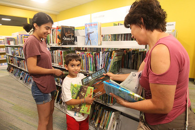 Candace H. Johnson-For Shaw Media Haley Portillo, 18, of Round Lake and her mother, Margarita, help her brother, Mark, 5, (center) pick out books in the Youth Services Department on the lower level during opening day of the new Lake Villa District Library at 140 N. Munn Road in Lindenhurst.  (8/5/19)