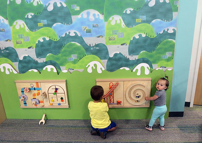 Candace H. Johnson-For Shaw Media Nathaniel Sfura, 4, of Lake Villa and his sister, Julianna, 1, play with an interactive play panel in the Youth Services Department on the lower level during opening day of the new Lake Villa District Library at 140 N. Munn Road in Lindenhurst.  (8/5/19)