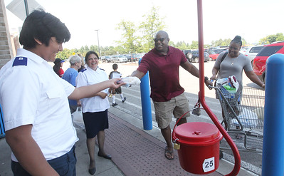 Candace H. Johnson-For Shaw Media James and Rebecca Deshazor, of Wadsworth (on right) hand Joshua Valladares, 13, of Waukegan, a volunteer, a bag of #2 pencils they were donating during the Salvation Army's Stuff the Bus at Walmart in Gurnee.Maritza Valladares, of Waukegan was standing next to her son, Joshua. (8/3/19)