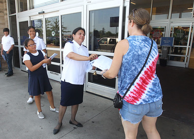 Candace H. Johnson-For Shaw Media Volunteer Maritza Valladares, of Waukegan (second from right) hands a needed school supply list to Allison Wisniewski, of Third Lake as she walks into Walmart during the Salvation Army's Stuff the Bus in Gurnee.Valladares' children, Joshua, 13, Hannah, 16, and Sarah, 10, were also handing out flyers and collecting donated school supplies. (8/3/19)