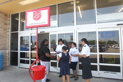 Candace H. Johnson-For Shaw Media A.J. Hughes, 21, talks with volunteers Maritza Valladares and her children, Joshua, 13, Sarah, 10, and Hannah, 16, all of Waukegan, on how to donate school supplies during the Salvation Army's Stuff the Bus at Walmart in Gurnee. (8/3/19)