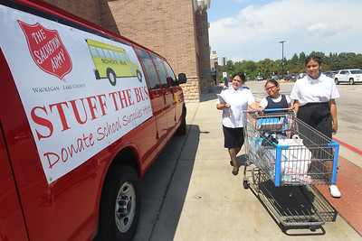 Candace H. Johnson-For Shaw Media Volunteers Maritza Valladares, of Waukegan and her daughters, Sarah, 10, and Hannah, 16, bring donated school supplies collected to an on-site large van during The Salvation Army's Stuff The Bus at Walmart in Gurnee. (8/3/19)