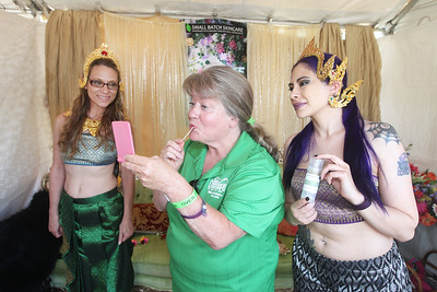 Candace H. Johnson-For Shaw Media Jane Yarnall, of Lindenhurst tries a new color of natural lipstick from a tester by the company, Fresh Skincare, with help from Thai princess models Bobbie Fleming of Fair Oaks, Ind., and Jessica McAlpin, of Roselle in their booth during Lindenfest at the Village Hall Center in Lindenhurst. (8/10/19)