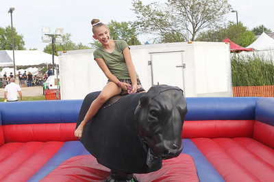 "Candace H. Johnson-For Shaw Media Kendall Day, 12, of Round Lake Beach rides ""Teddy"" the mechanical bull during Lindenfest at the Village Hall Center in Lindenhurst. (8/10/19)"