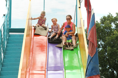 Candace H. Johnson-For Shaw Media Chelsea Yassinger, of Antioch goes down the Super Slide with her children Madelyn, 6, MacKenzie, 4, and Carter, 3, during Lindenfest at the Village Hall Center in Lindenhurst. (8/10/19)