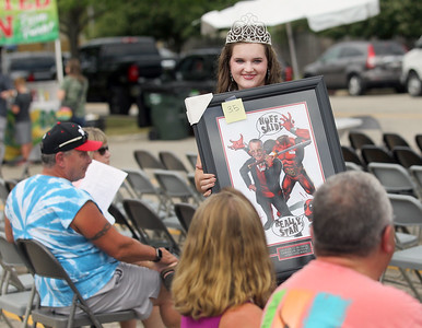 Candace H. Johnson-For Shaw Media Newly crowned Sydney Schmidt, 18, 2019 Miss Lindenhurst holds up a framed Stan Lee vs. Deadpool lithograph signed by artist Greg Horn as she walks through the crowd for bidders to see at the Lindenfest Mayor's Auction during Lindenfest at the Village Hall Center in Lindenhurst. (8/10/19)