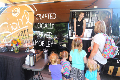 Candace H. Johnson-For Shaw Media Rachael Kveton, of Lake Villa takes an order from Lynn Goodman, of Lake Zurich, a nanny, with triplets Claire, Annie and Shannon O'Neill, all 2, and their big sister, Maggie, all of Libertyville at the Swirl Café coffee and food truck at the Libertyville Farmers Market.