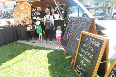 Candace H. Johnson-For Shaw Media Rachel Kveton, of Lake Villa takes an order from Carolyn Robinson, of Libertyville, a nanny, with Grace and Eleanor Kaostalanski, of Lake Bluff at the Swirl Café coffee & bakery food truck at the Libertyville Farmers Market.