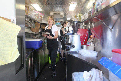 Candace H. Johnson-For Shaw Media Julie Compisi, of Deerfield works behind the scenes as Rachel Kveton, of Lake Villa takes orders at the Swirl Café coffee & bakery food truck at the Libertyville Farmers Market.