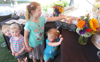 Candace H. Johnson-For Shaw Media Maggie O'Neill of Libertyville stands next to her sisters, Claire, Annie and Shannon, all 2, as she points out what baked goods she likes at the Swirl Café coffee & bakery food truck at the Libertyville Farmers Market.