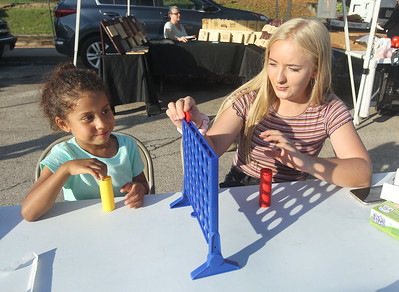 Candace H. Johnson-For Shaw Media Lareina Bell, 5, of McHenry plays Connect4 with Taylor Herriott, 16, of Round Lake at the Fox Lake Farmers Market on School Court in Fox Lake. The market runs on Tuesday nights from 4 -8:00 pm. through September. Taylor is a Grant Community High School NHS student who had volunteered at the market. (8/20/19)