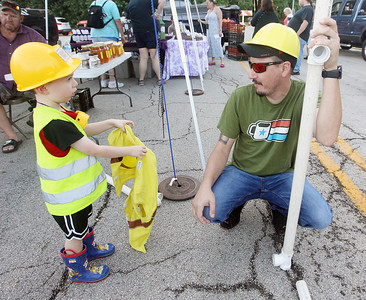 Candace H. Johnson-For Shaw Media Rhys Maniurka, 3, of Spring Grove tries to get his father, Matt, to put on a safety vest while playing in the Busy Brains Children's Museum area during the Fox Lake Farmers Market on School Court in Fox Lake. The market runs on Tuesday nights from 4 -8:00 pm. through September. (8/20/19)