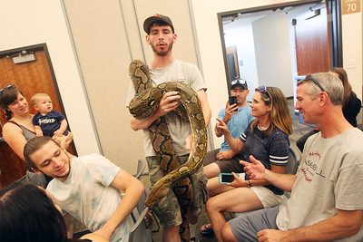 Candace H. Johnson-For Shaw Media Brendan Baker, entertainer/educator, walks through the audience carrying a reticulated python for everyone to see and touch during the Dave DiNaso's Traveling World of Reptiles show at the Fox Lake District Library. (8/24/19)
