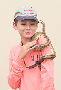 Candace H. Johnson-For Shaw Media Hayden Lundberg, 13, of Fox Lake holds a ball python during the Dave DiNaso's Traveling World of Reptiles show at the Fox Lake District Library. (8/24/19)