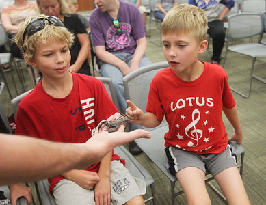 Candace H. Johnson-For Shaw Media Brendan Baker, entertainer/educator, holds a flat rock scorpion for Caden Hitzler, 11, and Daven Lundberg, 9, both of Fox Lake to see during the Dave DiNaso's Traveling World of Reptiles show at the Fox Lake District Library. (8/24/19)