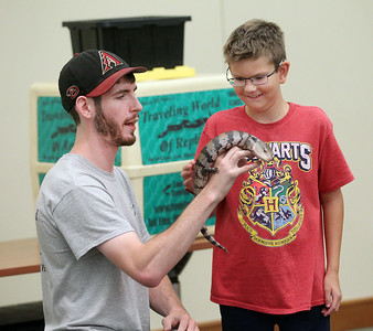 Candace H. Johnson-For Shaw Media Brendan Baker, entertainer/educator with Dave DiNaso's Traveling World of Reptiles, lets Caden Jones, 11, of Round Lake touch a blue-tongued skink during the show at the Fox Lake District Library. (8/24/19)