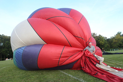 Candace H. Johnson-For Shaw Media Craig Maier, of Crystal Lake holds the envelope of the Featherlight II hot air balloon as it is filled up with cold air during the Color Aloft Balloon Festival at Central Park in Grayslake. (8/24/19)