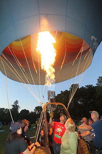 Candace H. Johnson-For Shaw Media Alan Zielinski, of Niles, (center) pilot and owner of the Featherlight II hot air balloon uses a propane burner to heat the air in the envelope during the Color Aloft Balloon Festival at Central Park in Grayslake. (8/24/19)
