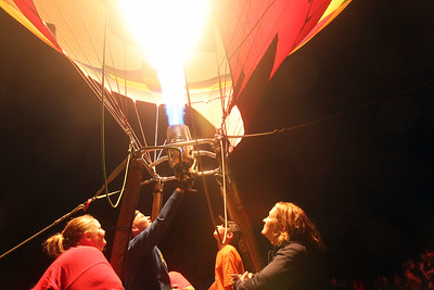 Jack Walter, of Waukesha, Wis., (second from left) uses a propane burner to heat up the envelope of the Kay's WindDancer II hot air balloon as Sarah Poznanski, of Mukwonago, Wis., and Jack's brother Ben, 12, and mother, Kay, stand close by during the Color Aloft Balloon Festival at Central Park in Grayslake. (8/24/19)