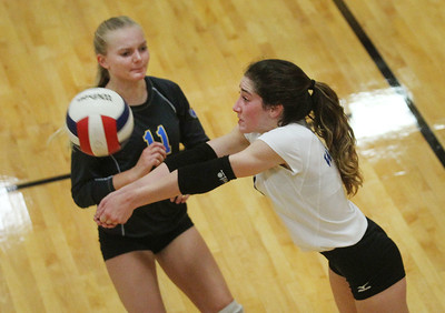 Candace H. Johnson-For Shaw Media Warren's Kayleigh Clickley stands close by as Ellie Columbus returns the ball against Carmel in the second set during the season opener at Carmel Catholic High School in Mundelein. Carmel won 25-12, 25-12. (8/26/19)