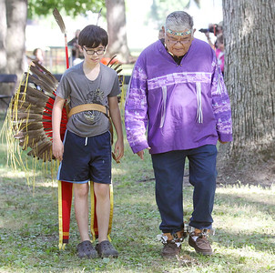 Candace H. Johnson-For Shaw Media John Martin Gamon, 10, of Zion learn how to dance by his grandfather, Martin Gamon, of Chicago for an intertribal dance during the 26th Annual Potowatomi Trails Pow Wow at Shiloh Park in Zion. (8/24/19)