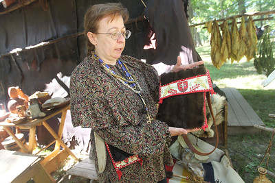 Candace H. Johnson-For Shaw Media Agi Hason, of Lansing shows a possibilities bag covered in fur with quill work used by a member of the Potowatami tribe in the 1750's on display during the 26th Annual Potowatomi Trails Pow Wow at Shiloh Park in Zion. (8/24/19)
