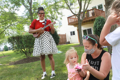 """Candace H. Johnson-For Shaw Media Nanny Nikki (Nikki Rung, of Fox Lake) sings the """"Happy Birthday"""" song to Lily Bajek, 3, as she gets ready to blow out her candles on a cupcake while her mother, Kristin, holds it during her birthday party at the Bajek's  home in Lake Villa. (8/5/20)"""