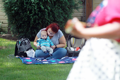 Candace H. Johnson-For Shaw Media Carmella Cain, of Lemont and her son, Graham, four-months-old, listen to Nanny Nikki (Nikki Rung, of Fox Lake) sing classic children's songs during a birthday party for Lily Bajek at the Bajek's home in Lake Villa. (8/5/20)