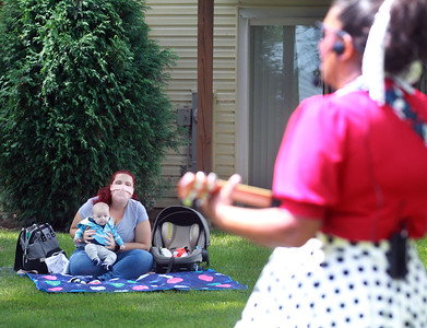Candace H. Johnson-For Shaw Media Carmella Cain, of Lemont and her son, Graham, four-months-old, listen to Nanny Nikki (Nikki Rung, of Fox Lake) sing classic children's songs during a birthday party for Lily Bajek at the Bajek's family home in Lake Villa. (8/5/20)