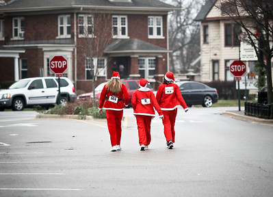 Josh Peckler - Jpeckler@shawmedia.com Women dressed as Santa walk down Williams Street in Downtown Crystal Lake after running in the Santa Run-Walk 5K for Kids in downtown Crystal Lake Sunday, December 2, 2012. Hundreds of runners dressed in Santa suits and reindeer antlers to raise money for children in Mchenry County.