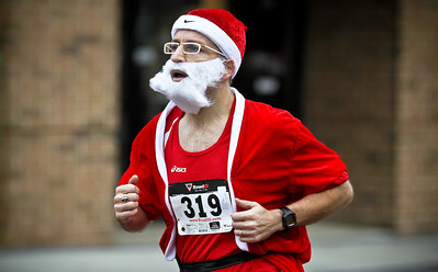 Josh Peckler - Jpeckler@shawmedia.com Steve Romer of Woodstock runs during in the Santa Run-Walk 5K for Kids in downtown Crystal Lake Sunday, December 2, 2012. Hundreds of runners dressed in Santa suits and reindeer antlers to raise money for children in Mchenry County.