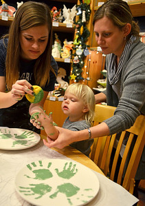 Monica Maschak - mmaschak@shawmedia.com Color Me Mine associate Tressa Bauer (left) applies a glaze paint to the hands of Jacey Wuhrman's two-year-old daughter Caleigh Wuhrman at the Crystal Lake store on Tuesday, December 4, 2012.  The Wuhrmans decided to decorate Christmas plates with the hand and foot prints of their three children.